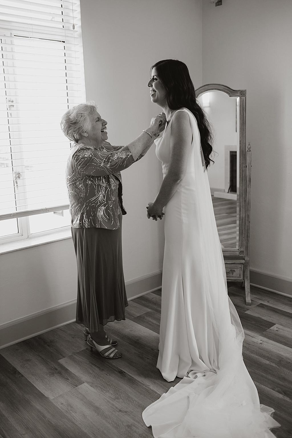 grandma helping bride with jewelry