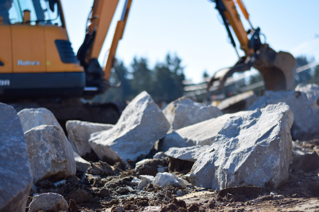 Earthmover focused on Boulder Wall Construction from your Breaking Ground Excavation Contractor