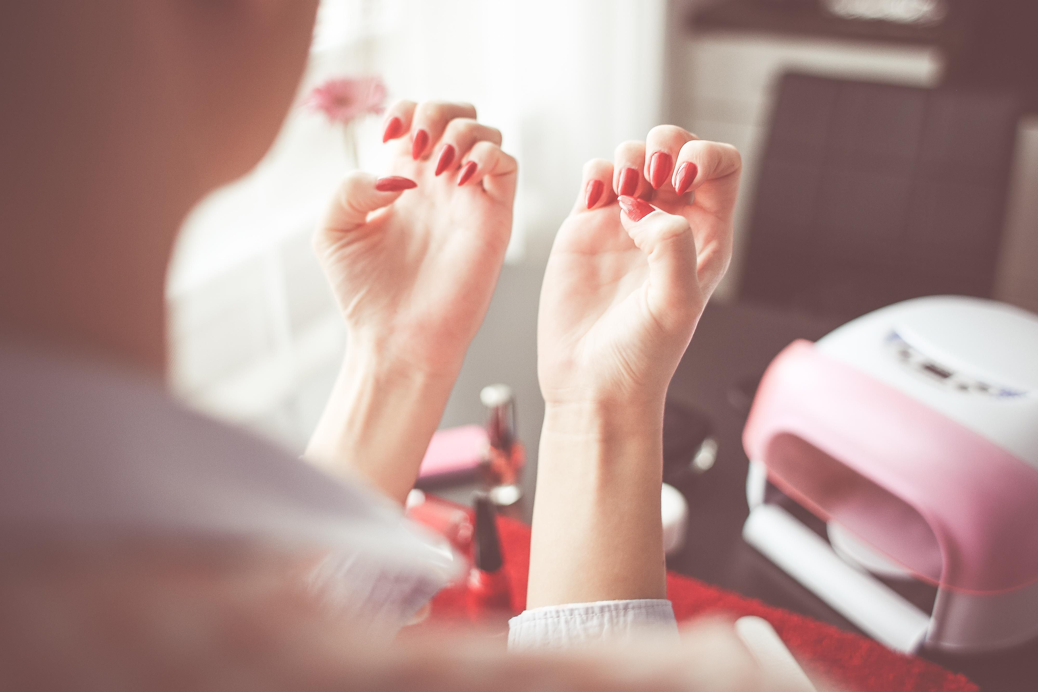 Woman inspecting her freshly painted red nails