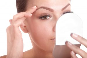 Young woman looking into makeup mirror.
