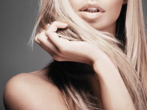 Beautiful woman with long straight blond hair. Fashion model pos
