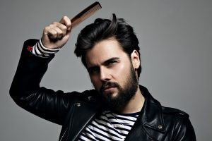 bearded man feigns combing his hair