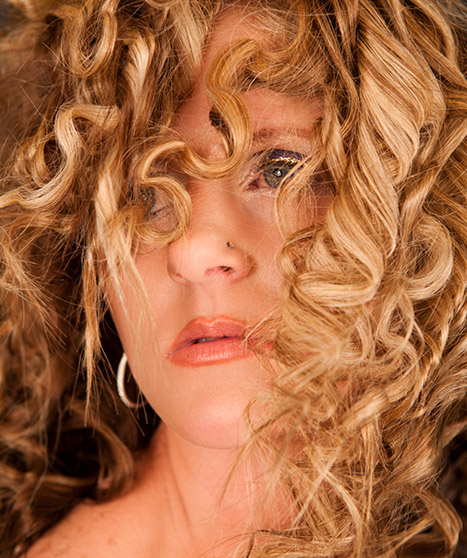 Woman with very curly brown-blonde hair