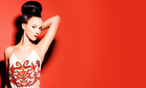 model with dark hair updo on a red background