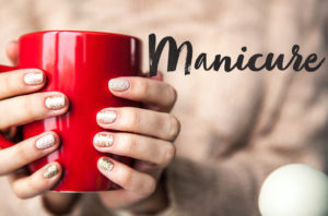 woman with manicure holding red mug