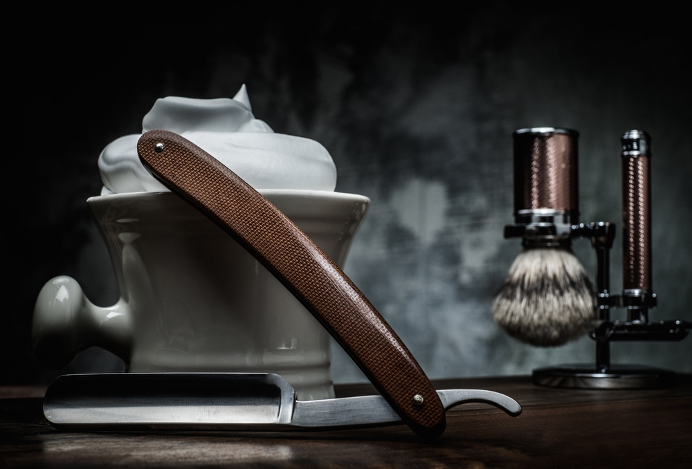 barbers tools with shaving cream on dark background