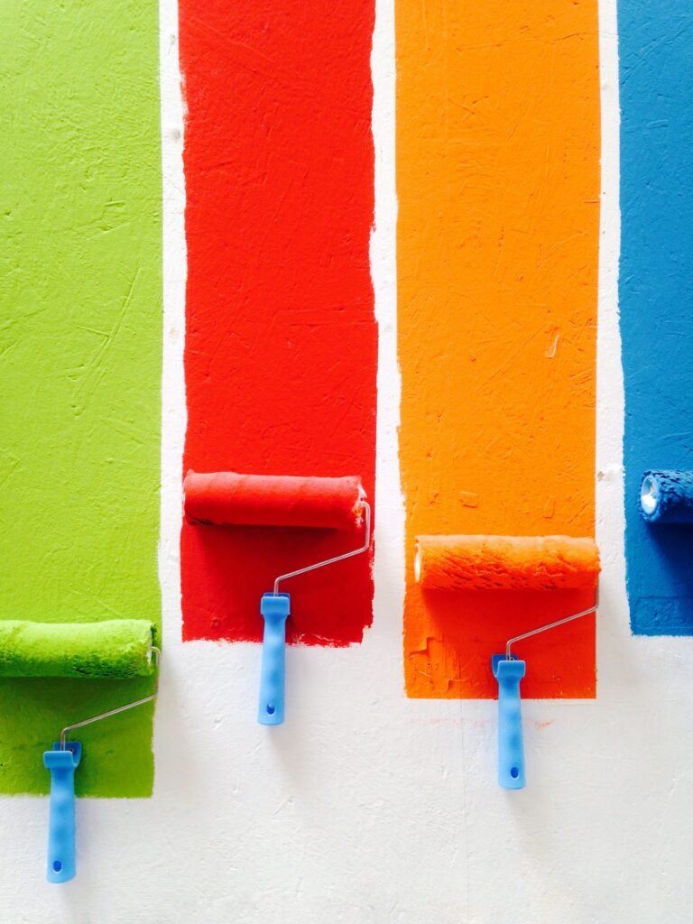 four brightly-colored paint samples on the wall: green, red, orange, and blue