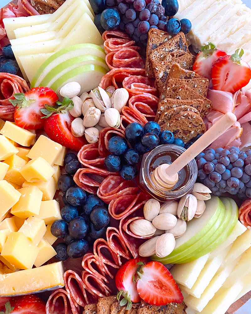 close up of charcuterie board with blueberries, strawberries, apples, honey, cheese, meats, and crackers