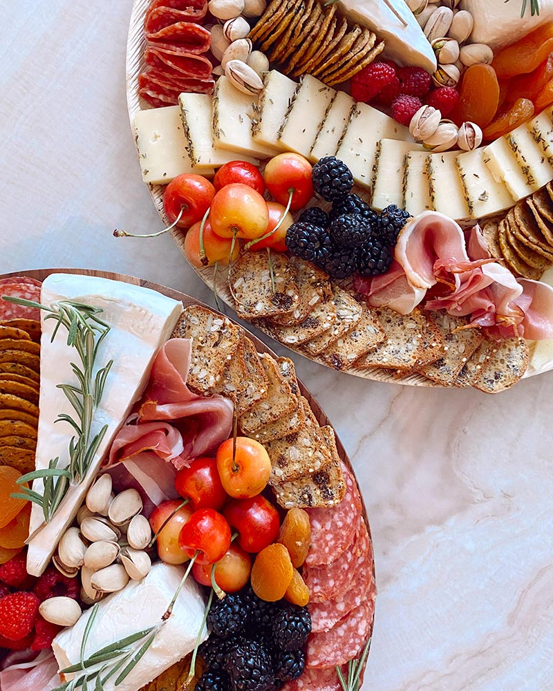 two round charcuterie boards with cherries, blackberries, cheese, meats, and nuts