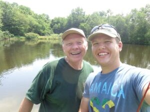 John Jackson and young man with Jamaica missions trip t-shirt smiling with fishing pond behind them