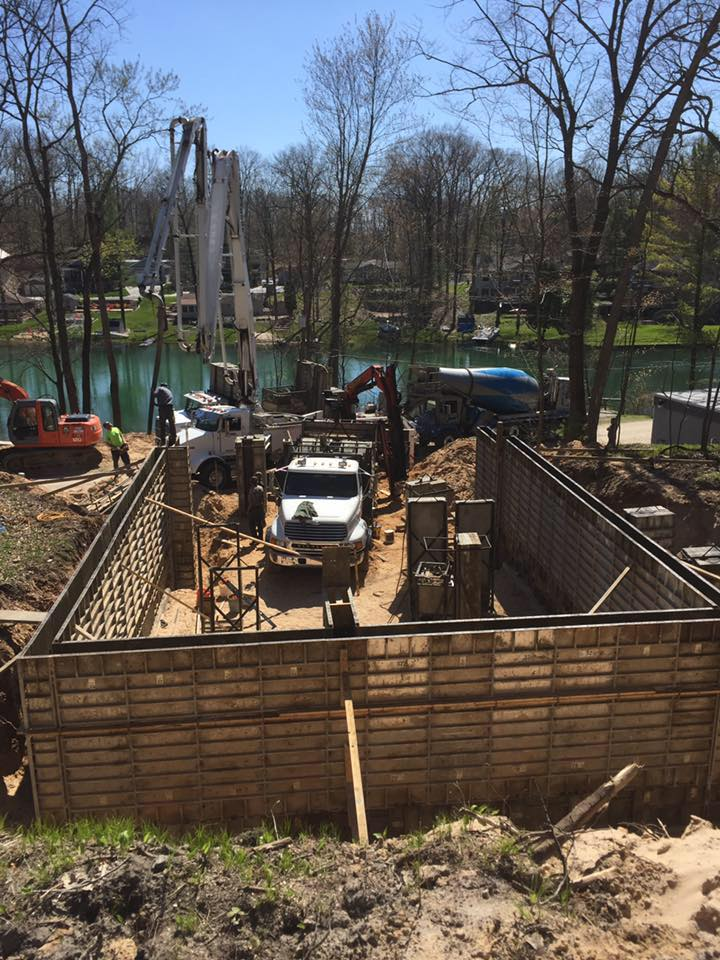 Crews pouring concrete walls for house with river view