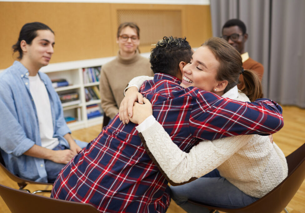 Portrait of two young women hugging in support group meeting, both smiling happily, copy space