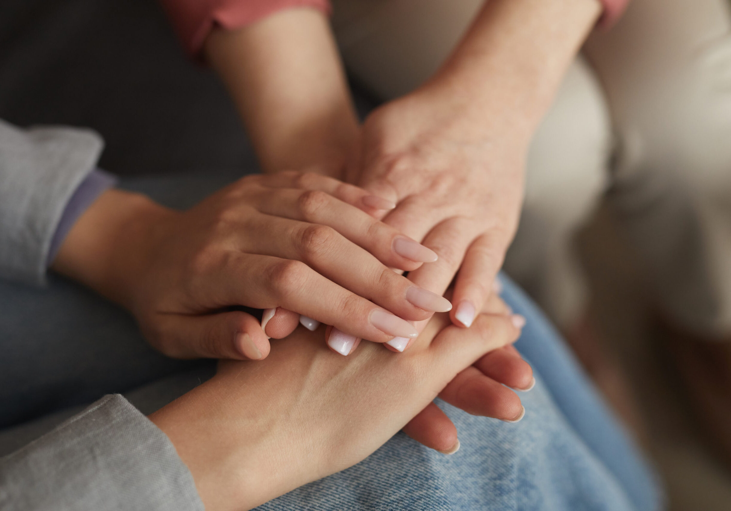Close-up of women sitting on sofa and holding hands they supporting each other