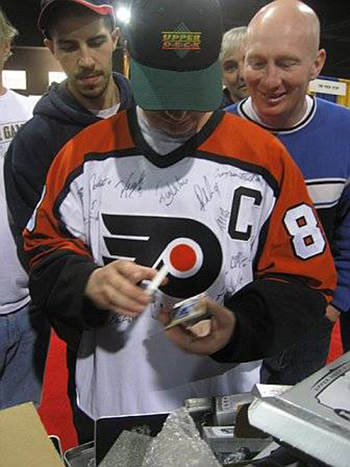 People gathering around to see a collector open up packs of Upper Deck NHL cards