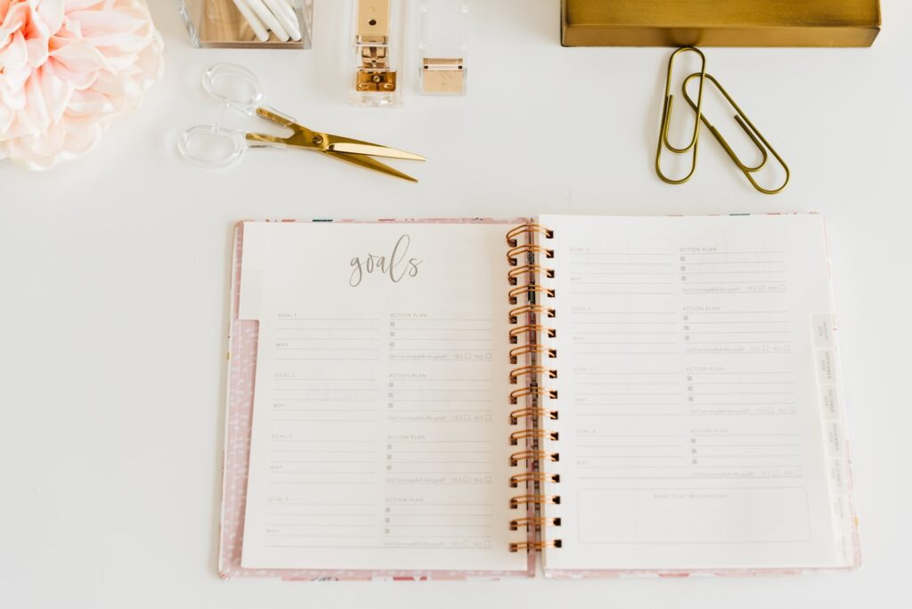 scissors and two paper clips beside opened spiral notebook