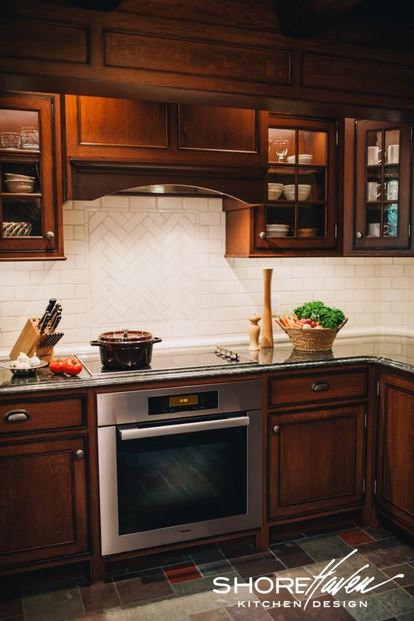 Framed herringbone tile detail above cooktop.