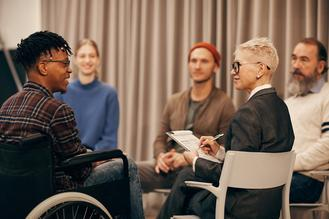 Young African man in wheelchair talking to mature woman while she making notes during therapy lesson