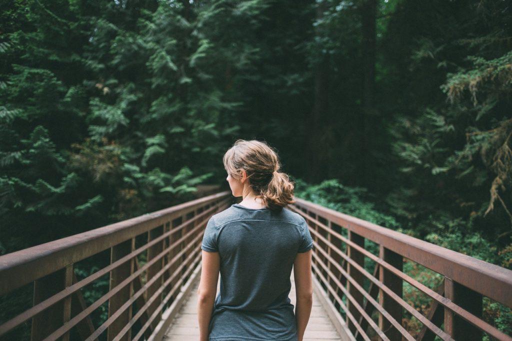 Girl walking across a bridge