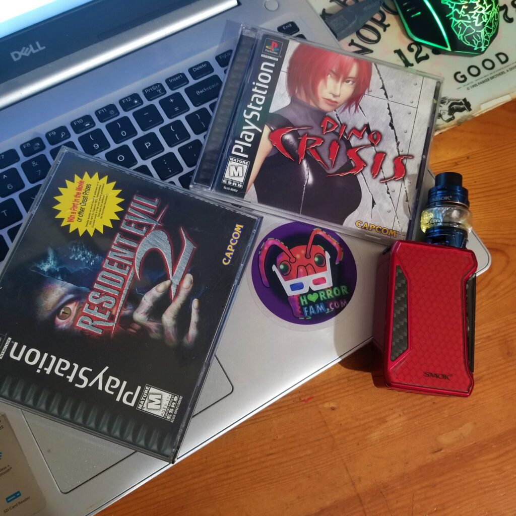 Resident Evil 2, Dino Crisis, a laptop, a HorrorFam.com sticker, and a vape mod