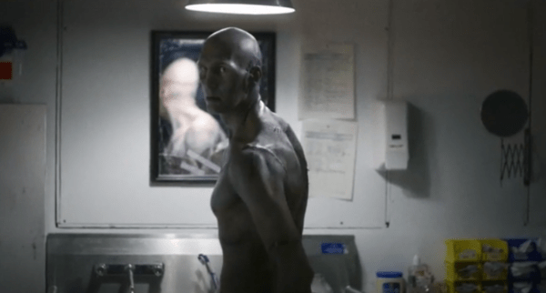 Bald heavily-scarred man with stitches standing in a bathroom in Depraved