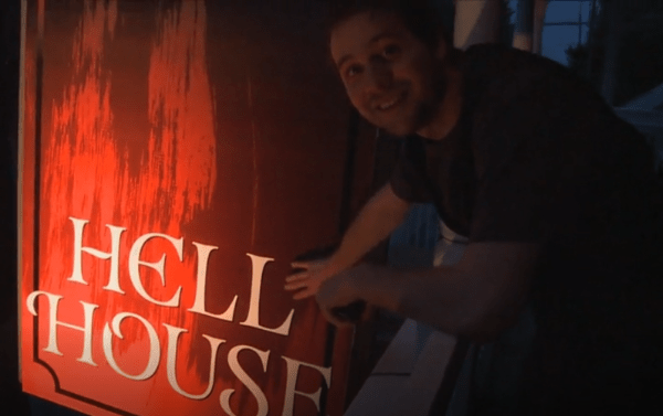 Man smiling pointing to a sign that says Hell House