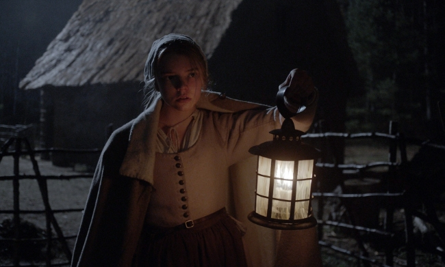 Screenshot from The Witch / The VVitch of a puritan girl holding up a lantern in the dark