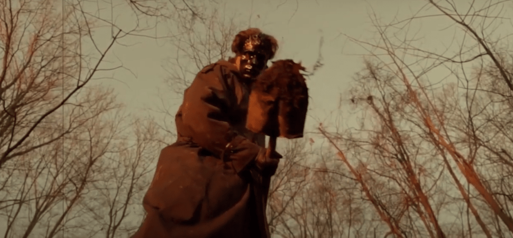 Screenshot from Goodnight Daddy of a masked man with a dirty shovel