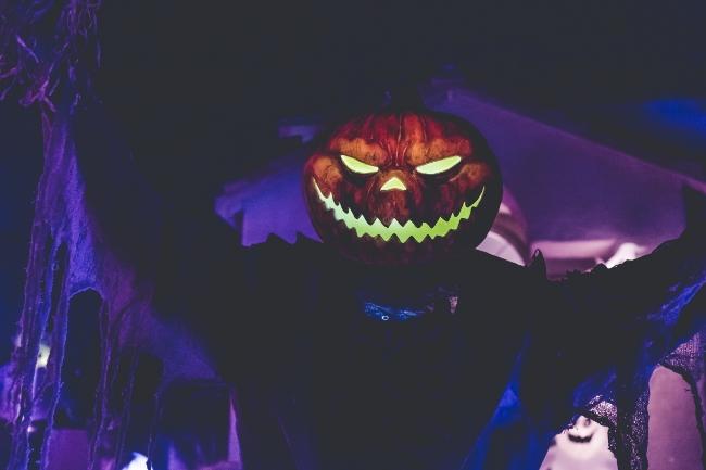 scarecrow with a lit Jack-o-lantern head