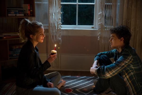 Girl holding a cupcake with a candle while a boy looks on in Happy Death Day