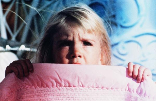 girl hiding under her blanket in Poltergeist