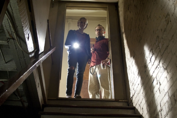 Two people looking down the stairs of a basement in The Innkeepers