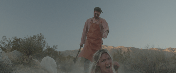 man in a butcher's apron and skin  mask with an ax chasing down a terrified woman.