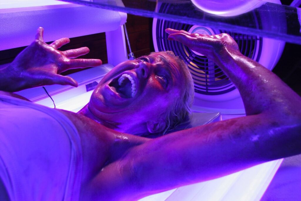 a girl stuck in a tanning booth in Final Destination 3, wide-eyed, open mouth, blue lighting.