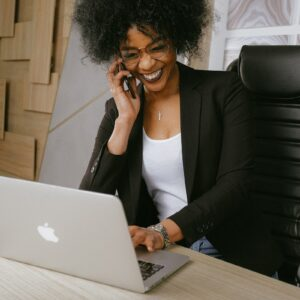 Mulher sentada em frente a um notebook, falando ao telefone