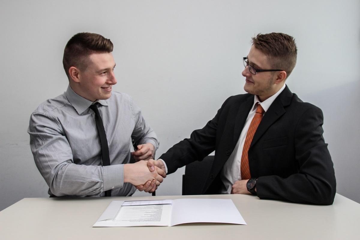 Dois homens sentados em uma mesa se cumprimentando com aperto de mãos