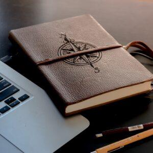 Notebook e caderno de anotações com uma bússola desenhada na capa