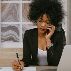 Executiva negra falando ao celular e escrevendo em uma folha, com notebook ao lado