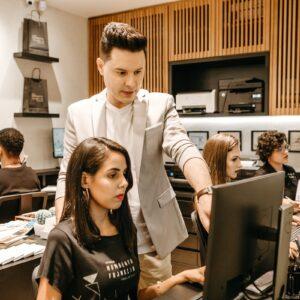 Homem ensinando mulher da equipe no escritório