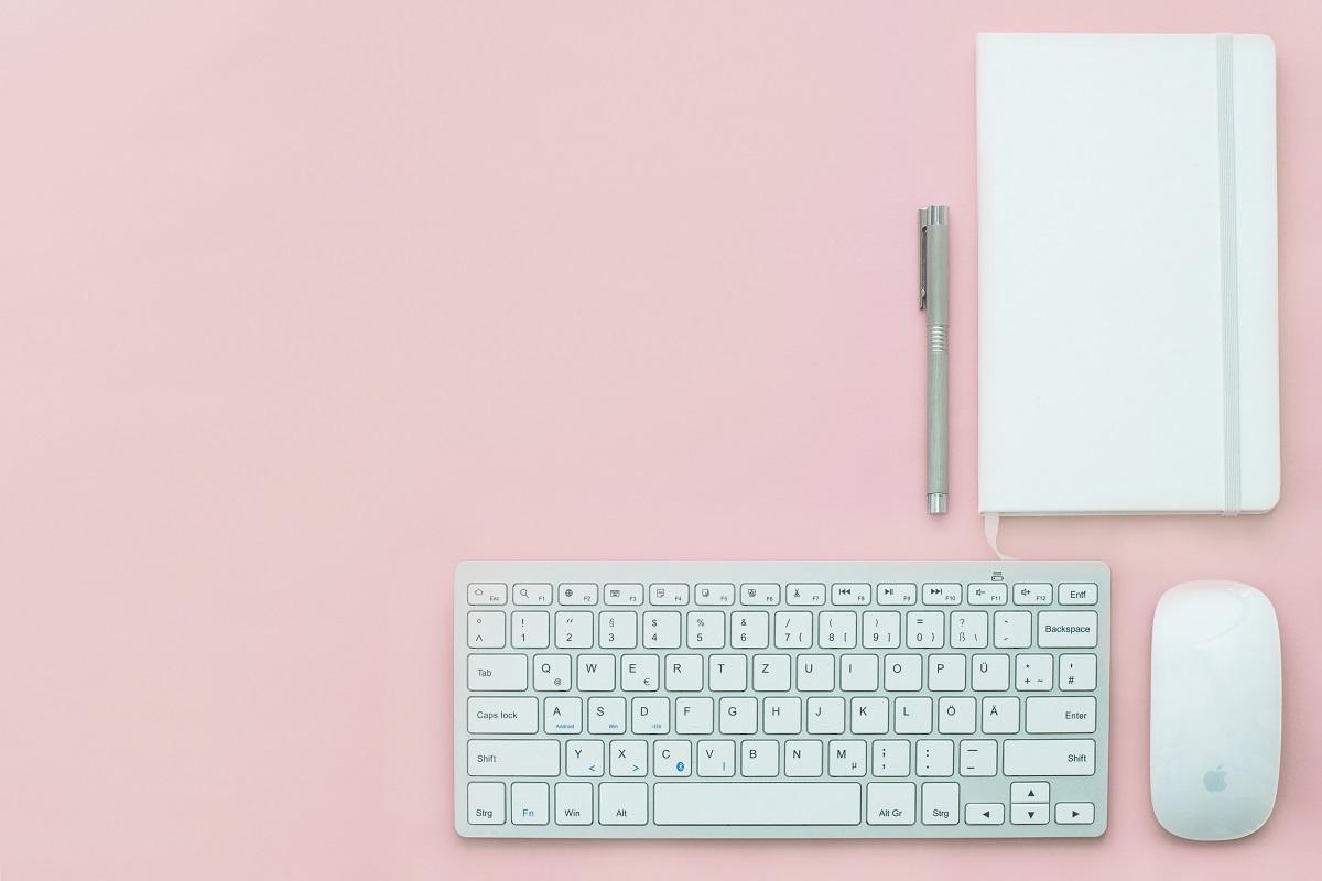teclado, mouse, caneta e caderno de anotações organizados em cima de uma mesa