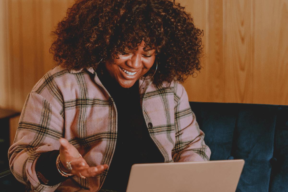 Mulher negra com computador na mão trabalhando na área de sucesso do cliente