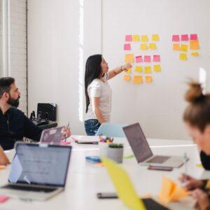 Homens e mulheres em um escritório trabalhando com post its