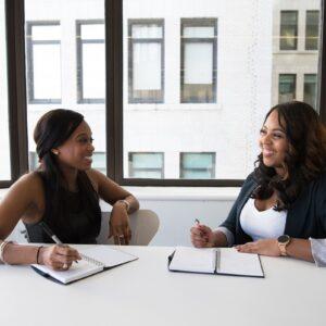 Duas mulheres negras conversando e fazendo anotações em seus cadernos