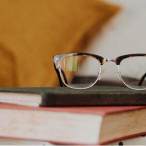 Dois livros empilhados e um óculos no topo da pilha