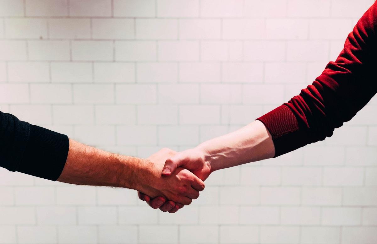 Duas pessoas se cumprimentando com um aperto de mãos em frente a uma parede branca