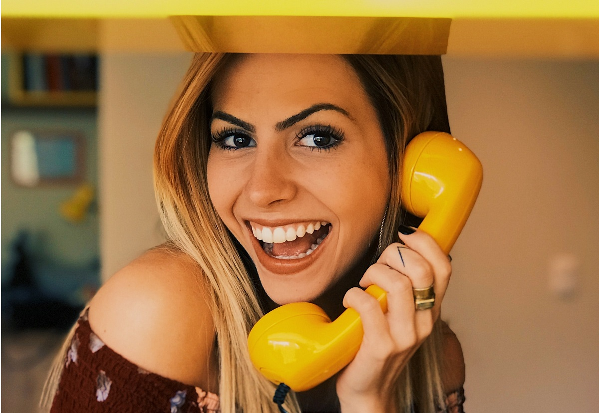 Mulher sorrindo com um telefone amarelo na mão
