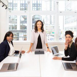 Um homem e três mulheres sentados ao redor de uma mesa com seus notebooks enquanto outra mulher se posiciona em pé ao centro da mesa