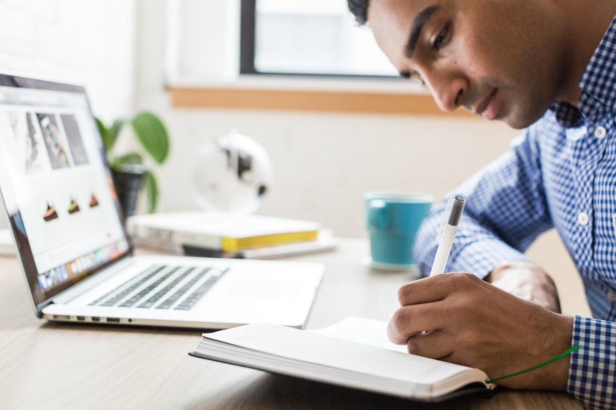 Homem sentado em uma cadeira em frente ao notebook, escrevendo em um caderno