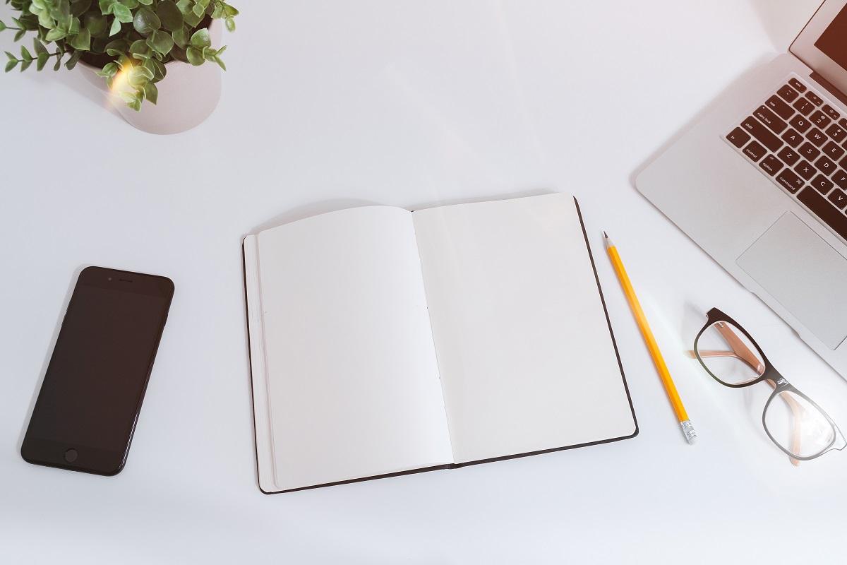 Livro, caneta, notebook, celular e óculos em cima de uma mesa