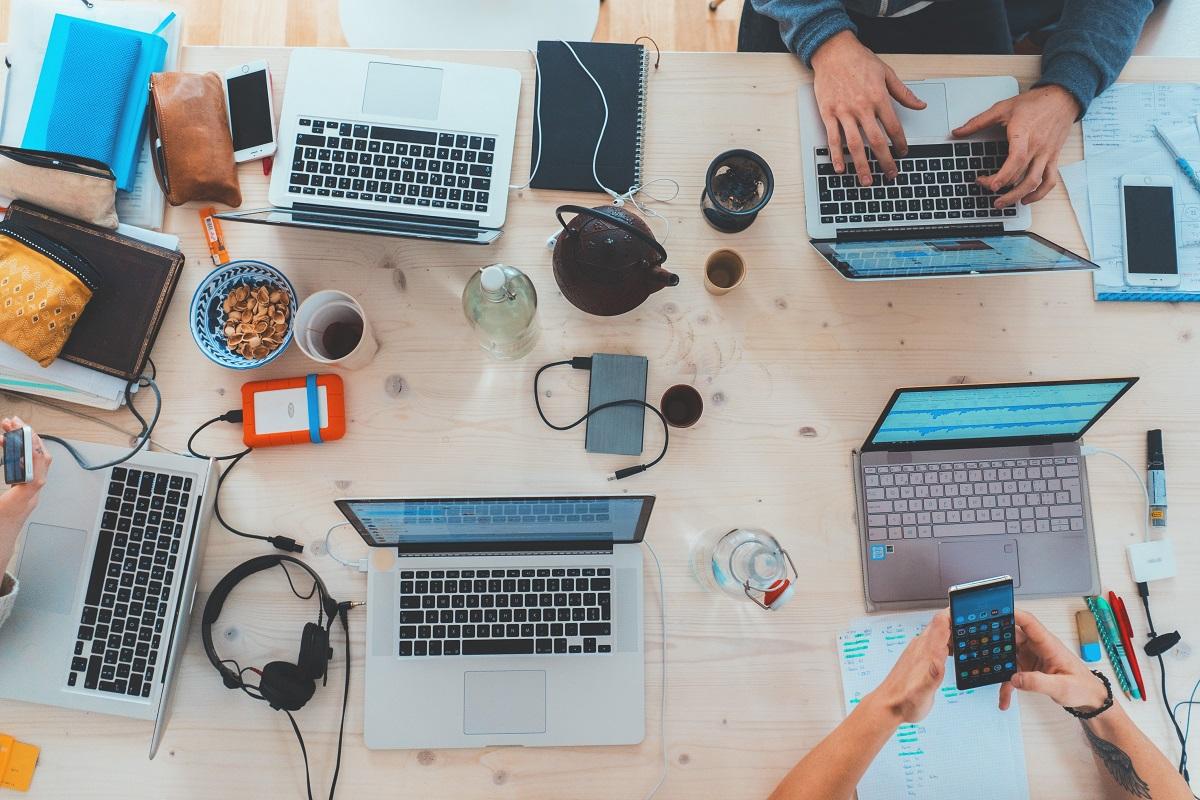 Pessoas sentadas ao redor de uma mesa com notebooks, smartphones e phones