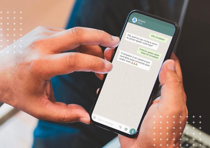 Mão segurando celular com tela aberta no WhatsApp da Octadesk